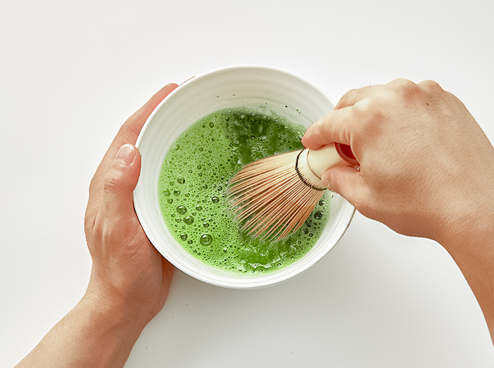 hand whisking japanese matcha green tea in a chawan bowl