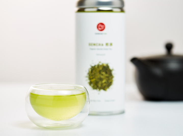 senbird-organic green tea being being served in a clear glass cup with tea canister and black kyusu teapot in the background