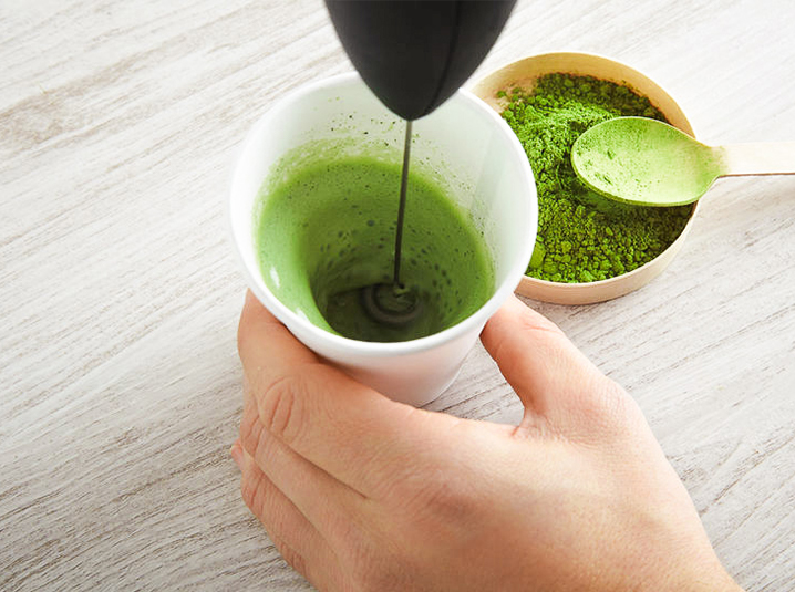 a blender whisking a matcha in a white cup with matcha powder and teaspoon next to it