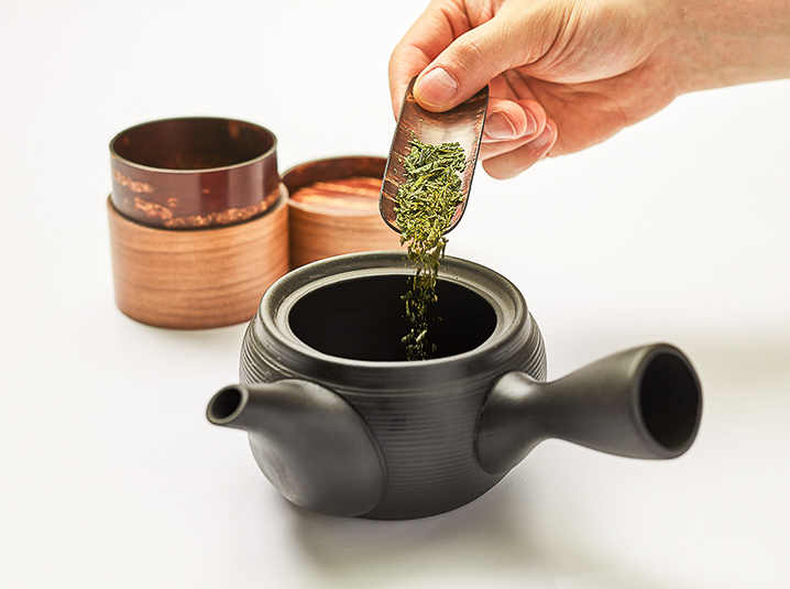 hand pouring green tea from sakura chasen teaspoon into a black kyusu teapot with sakura cherry blossom tea canisters in the background