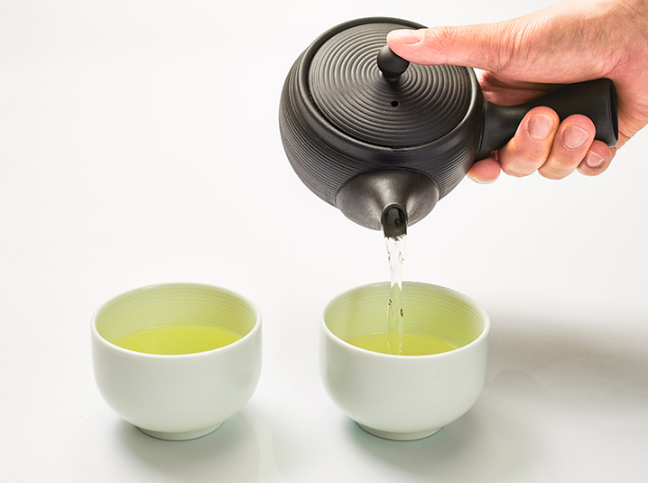 A hand pouring green tea into two cups using a Japanese traditional kyusu teapot